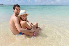 Couples embrassant se reposer en eau de mer clair comme de l'eau de roche Images stock