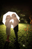 Couples embrassant sous le parapluie Photos stock