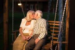 Couples embrassant sur l'oscillation de porche Photographie stock