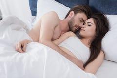 Couples embrassant tandis que sommeil image libre de droits