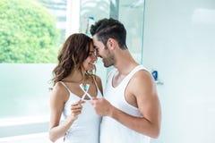 Couples embrassant tout en tenant la brosse à dents Photos libres de droits
