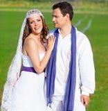 Couples en étreinte de jour du mariage dans le pré vert Image stock