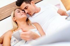Couples en café potable de matin d'amour dans le lit Image stock