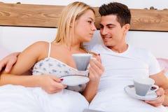 Couples en café potable de matin d'amour dans le lit Photo libre de droits