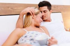 Couples en café potable de matin d'amour dans le lit Photographie stock