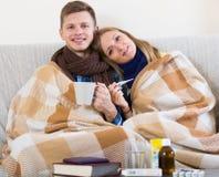Couples en difficulté sous la couverture vérifiant la fièvre Image libre de droits