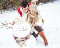 Couples en hiver construisant un bonhomme de neige Photos libres de droits