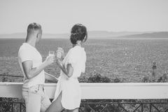 Couples en jus potable d'amour sur le balcon, la nature et la mer sur le fond L'homme et la dame dans le peignoir tiennent le ver Image stock