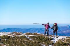 Couples en montagnes recherchant la bonne manière Photographie stock
