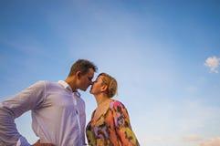 Couples en portrait de baiser d'amour avec les vêtements d'été et le ciel clair Photo stock