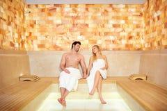 Couples en serviettes se reposant dans le sauna Images stock