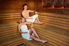 Couples en serviettes se reposant dans le sauna Photos stock