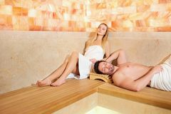 Couples en serviettes se reposant dans le sauna Image stock