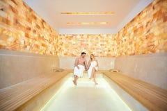 Couples en serviettes se reposant dans le sauna Photographie stock