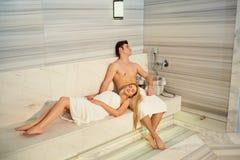 Couples en serviettes se reposant dans le sauna Photo libre de droits