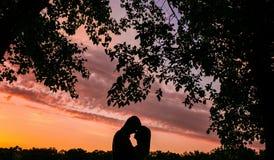 Couples en silhouette d'amour pendant le coucher du soleil Images stock