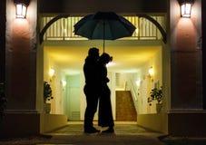 Couples en silhouette embrassant sous le parapluie Image libre de droits