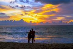 Couples en soleil de observation d'amour au coucher du soleil sur la plage, Phuket Thaila Photos libres de droits