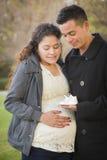 Couples enceintes d'hispanique tenant des chaussures de bébé dehors Photos stock