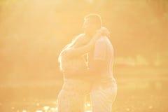 Couples enceintes dans les rayons de la lumière du soleil au coucher du soleil Étreintes de mari Photographie stock libre de droits