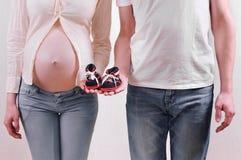 Couples enceintes de jeunes dans des jeans attendant un bébé garçon tenant le litt Image stock