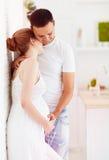 Couples enceintes de jeunes dans l'amour, étreignant à la maison Image stock