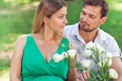 Couples enceintes de jeunes dans l'amour regardant l'un l'autre Image libre de droits