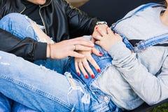 Couples enceintes de jeunes tenant des mains sur le grand ventre Image stock