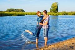 Couples enceintes heureux et de jeunes ayant l'amusement sur la plage Été Image stock