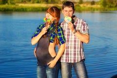 Couples enceintes heureux et de jeunes ayant l'amusement sur la plage Été Photo stock