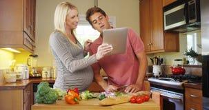 Couples enceintes heureux fonctionnant ensemble dans la cuisine Photographie stock libre de droits