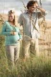 Couples enceintes heureux restant ensemble à la plage photo stock
