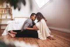 Couples enceintes romantiques se reposant sur le plancher Image stock