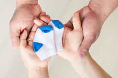Couples enceintes tenant de petites chaussettes Photographie stock libre de droits