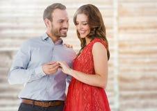 Couples engagés heureux regardant la bague de fiançailles Photo stock