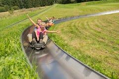 Couples Enjoying Alpine Coaster Luge stock photography