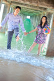 Couples enjoying on the beach Stock Photos