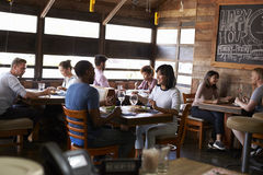 Couples enjoying lunch in a busy restaurant Stock Image