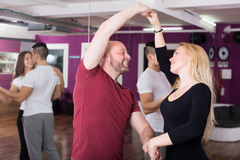 Couples enjoying of partner dance. Cheerful couples enjoying of partner dance indoor Stock Images