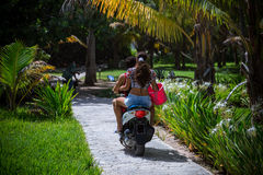 boy and girl enjoying riding the motor scooter Stock Images