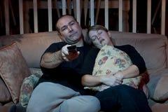 Couples ennuyés regardant la TV photographie stock