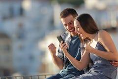 Couples enthousiastes célébrant des nouvelles en ligne de téléphone dehors photo libre de droits
