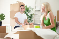 Couples enthousiastes dans la nouvelle maison déballant des boîtes Photos stock