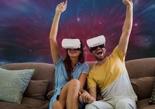 Couples enthousiastes dans le casque de VR se reposant sur le fond de galaxie Photo libre de droits