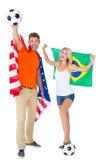 Couples enthousiastes de passioné du football tenant les Etats-Unis et le drapeau de brazils Photographie stock libre de droits