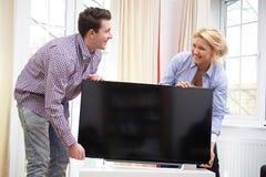 Couples enthousiastes installant la nouvelle télévision à la maison Image libre de droits