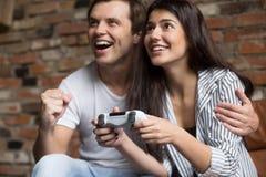 Couples enthousiastes jouant des jeux vidéo d'ordinateur ensemble Images stock