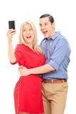 Couples enthousiastes prenant un selfie avec le téléphone portable Images libres de droits