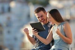 Couples enthousiastes vérifiant le contenu en ligne de comprimé dans une ville image libre de droits