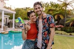 Couples entièrement humides par la piscine avec une arme à feu d'eau Photographie stock